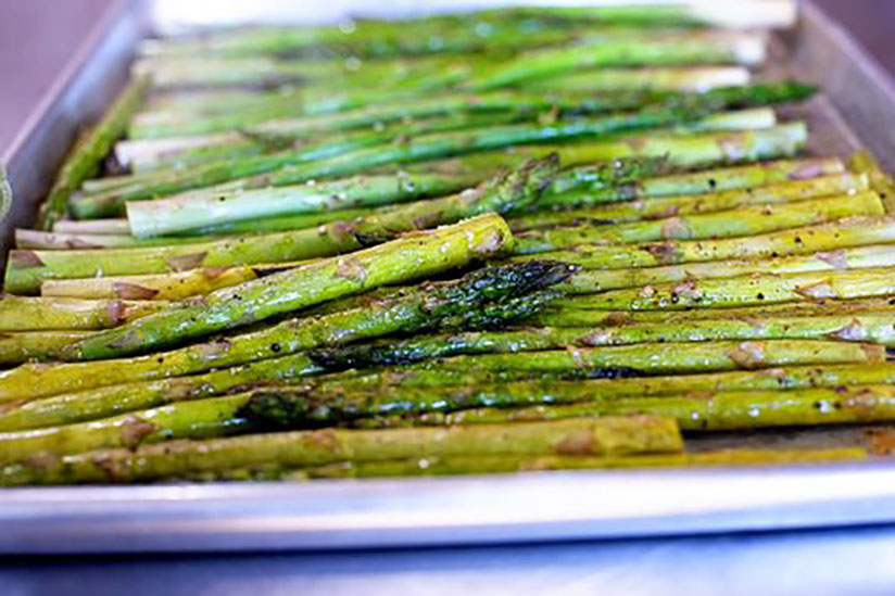 Oven roasted asparagus stalks on baking tray on counter
