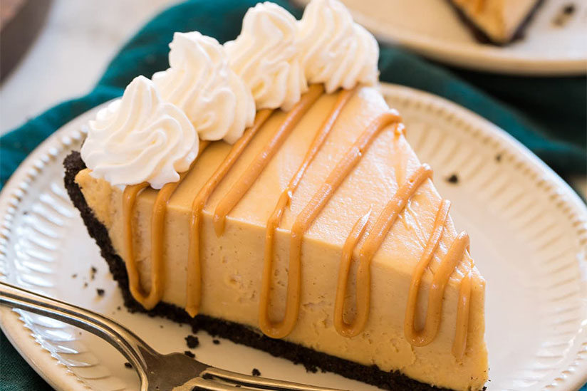 Slice of peanut butter pie with whipped cream on paper plate with fork