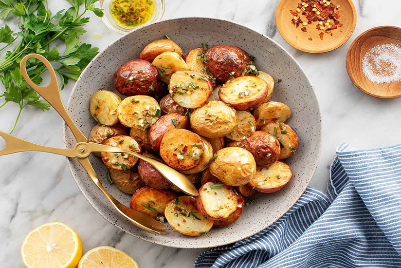 Halved oven roasted potatoes in bowl with tongs on marble counter