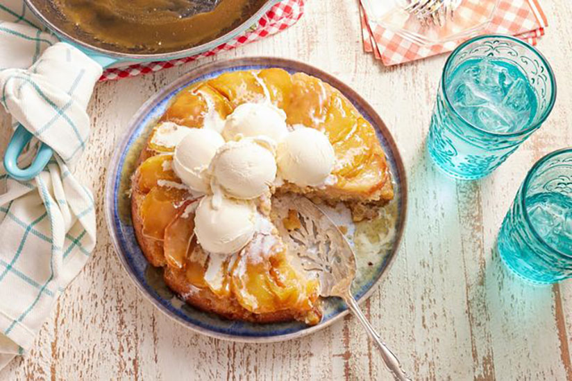Consumed apple cake topped with scoops of vanilla ice cream on plate
