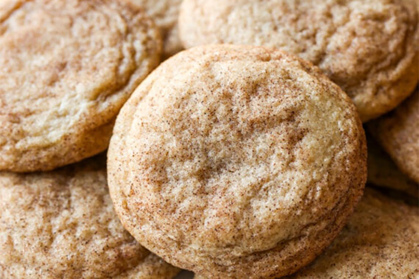 Pile of snickerdoodle cookies sprinkled with cinnamon on plate