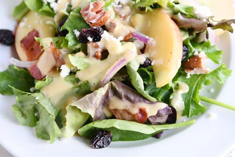 Spinach salad with raisins, chopped bacon, and red onions on plate