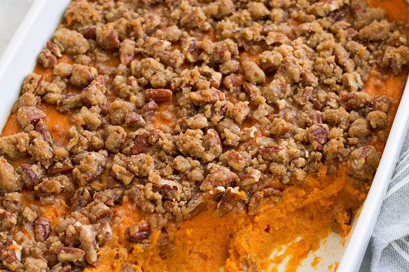 Sweet potato casserole topped with cinnamon and pecans in white dish
