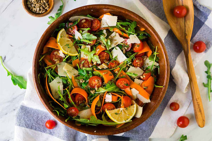 Arugula salad with tomatoes, carrots, and parmesan cheese in wood bowl