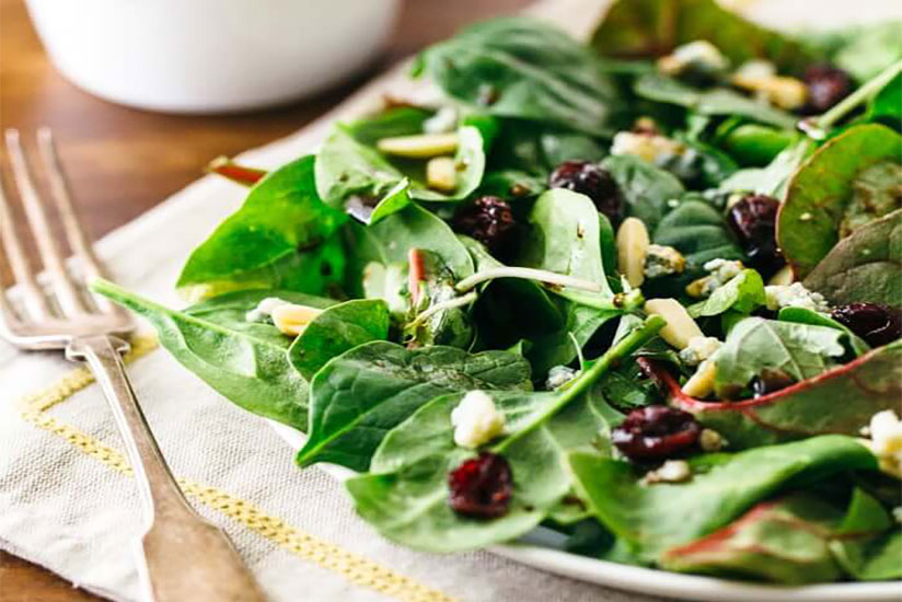 Green salad with dried cherries and almonds on plate beside fork on table