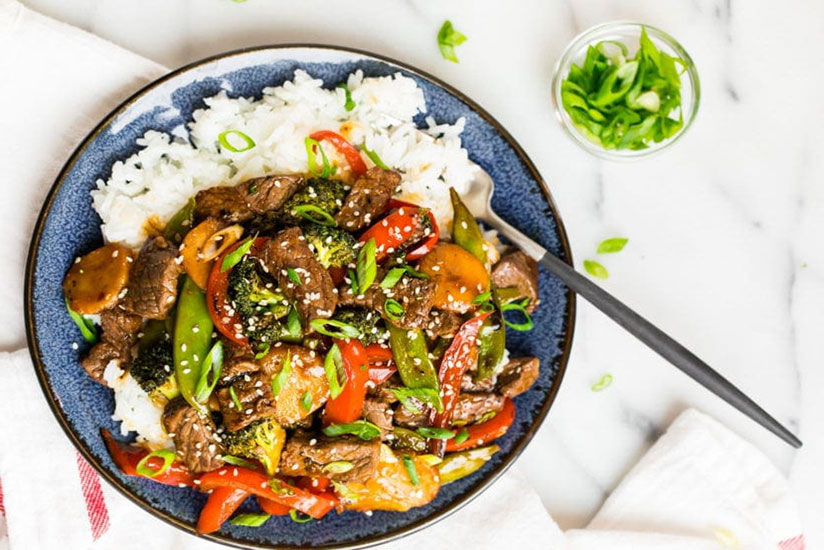Beef stir fry on bed of rice topped with chopped green onions on blue plate