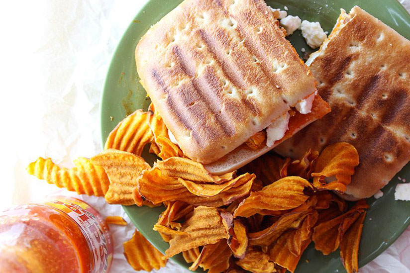 Buffalo chicken grilled cheese panini with side of chips on green plate