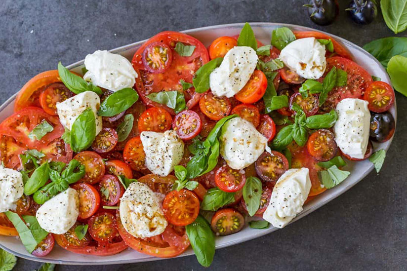 Tomato salad with burrata cheese and basil sprinkled with pepper in white dish