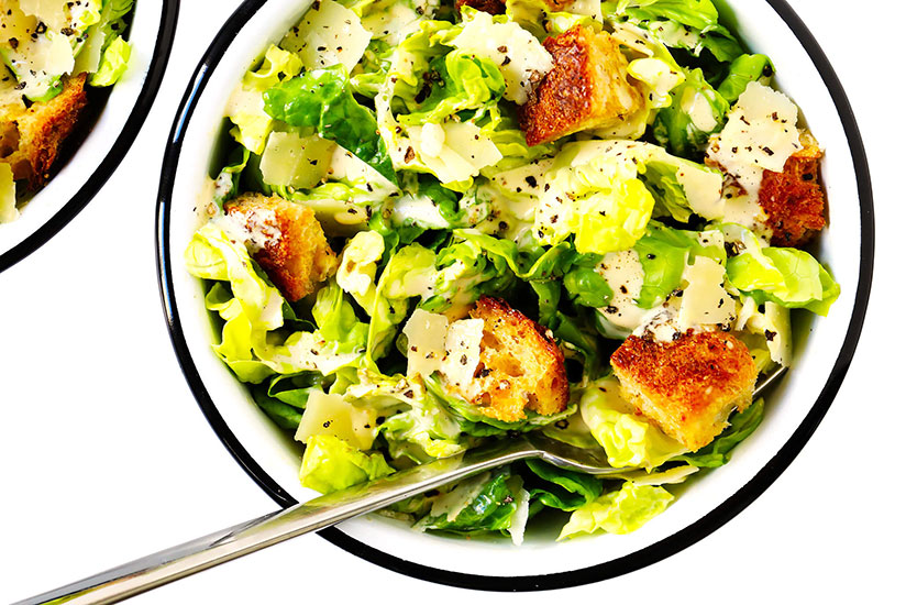Two bowls of caesar salad with homemade dressing with metal spoon on counter