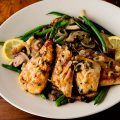 Chicken piccata with green beans and lemon on plate