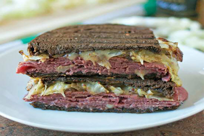 Halved corn beef and cabbage pressed sandwich on white plate on counter