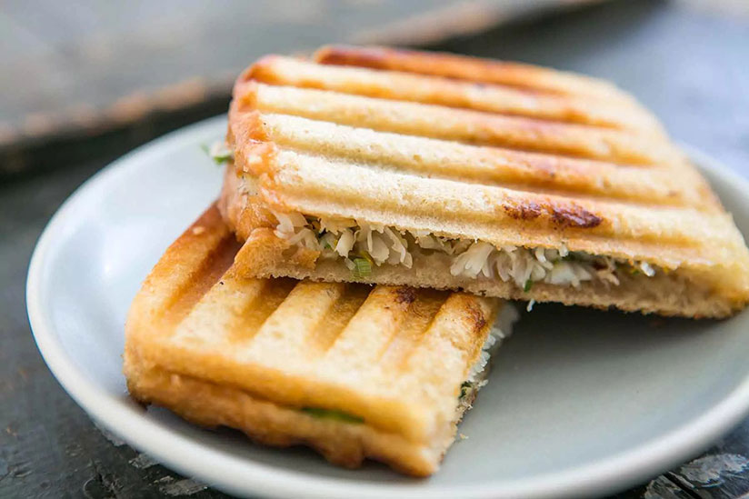 Halved crab salad panini on sourdough bread on plate on counter