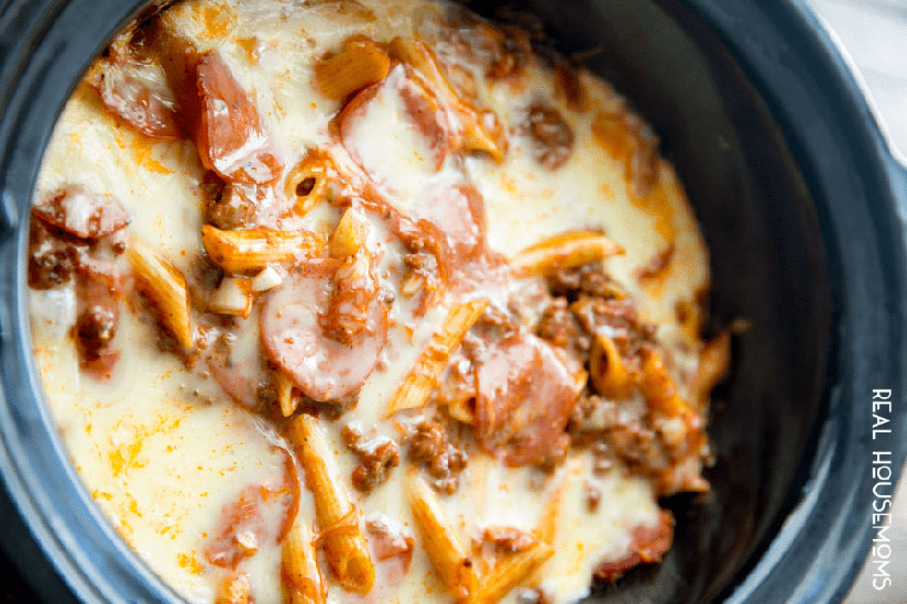 Pizza casserole cooking inside crockpot with melted cheese on top on counter