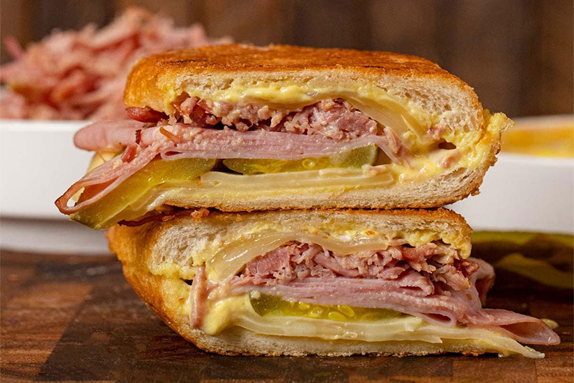 Cuban panini with layers of melted cheese, ham, and pulled pork on counter