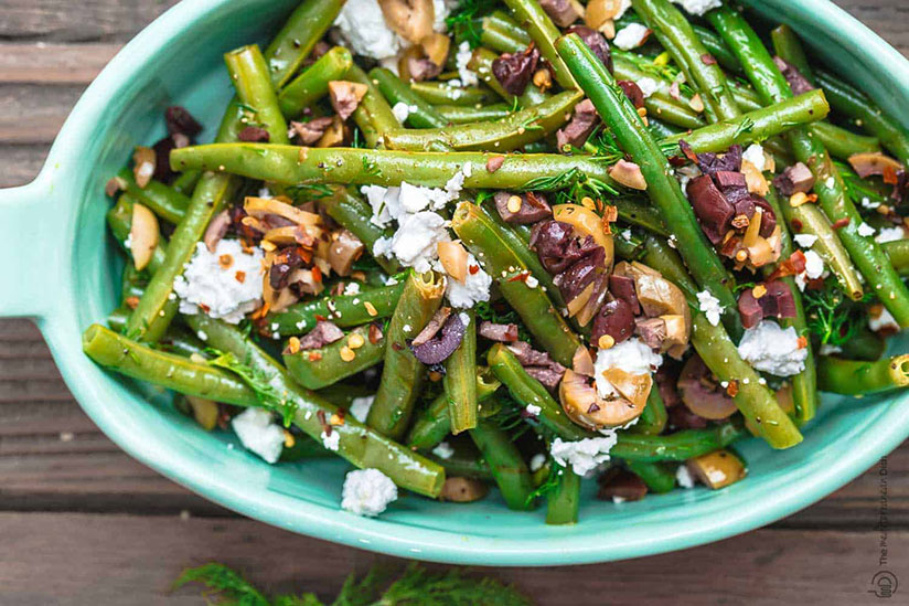 Greek green bean salad sprinkled with crumbled feta cheese in green dish