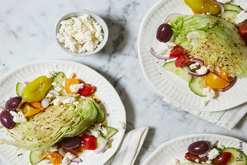 Three plates of iceberg lettuce surrounded by Greek wedge salad and feta cheese