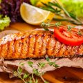 Grilled salmon with tomatoes and lemon on wood chopping board