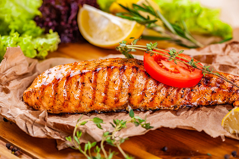 Grilled salmon topped with slice of tomato and herbs on wood board