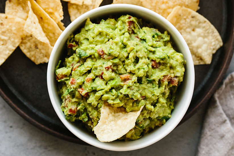 Tortilla chip dipped in guacamole in white bowl on top of black circular tray