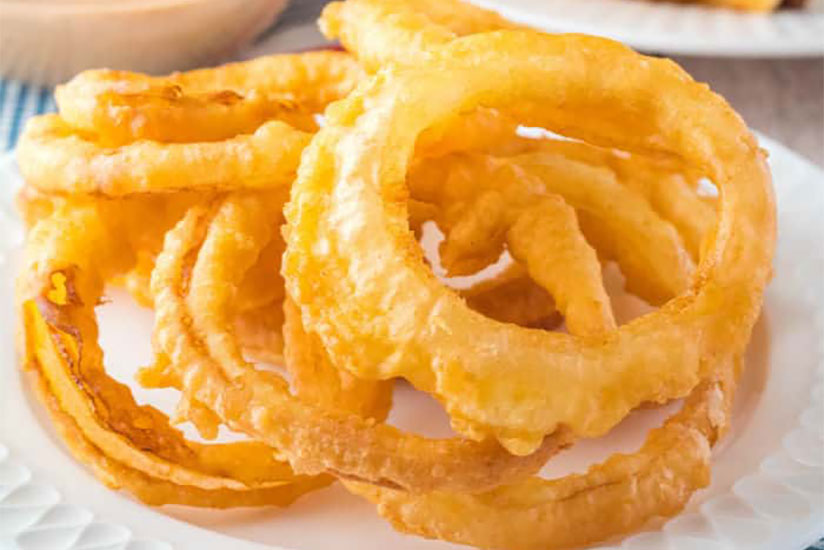 Deep fried crispy onion rings on white plate on table