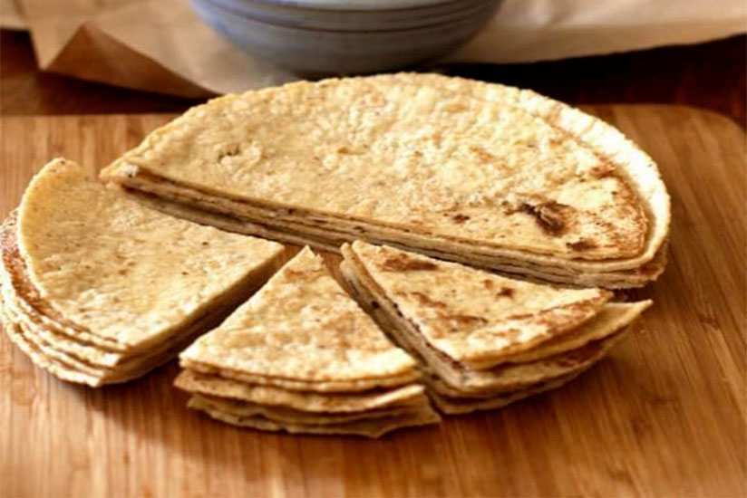 Baked homemade tortilla chips cut in half and quarters on wood tray
