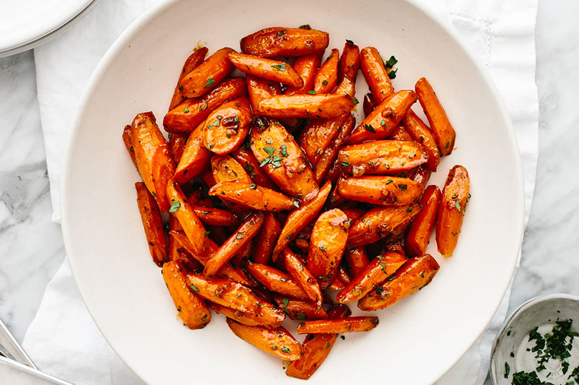 Chopped honey glazed carrots sprinkled with green onions on white plate
