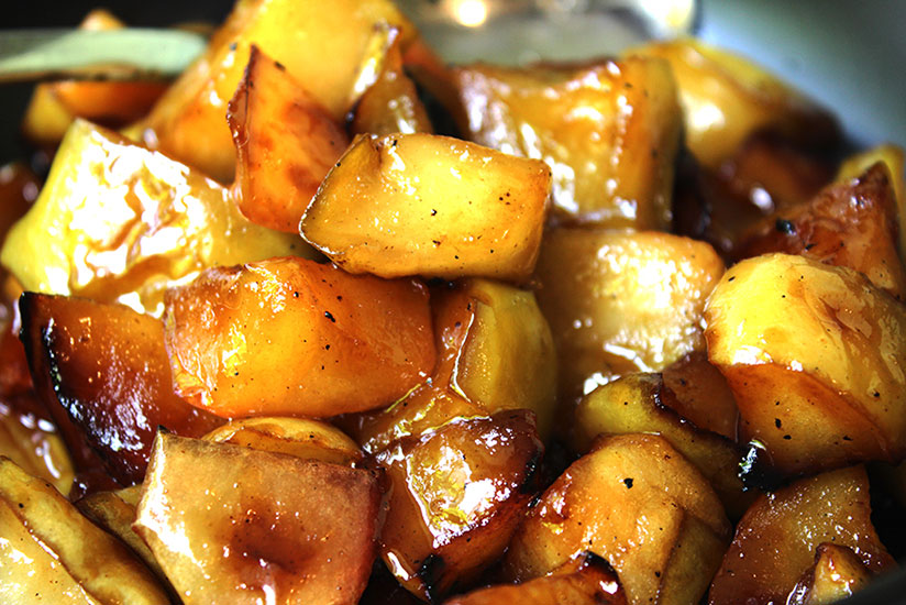 Piled of cubed honey roasted apples in pan on green background
