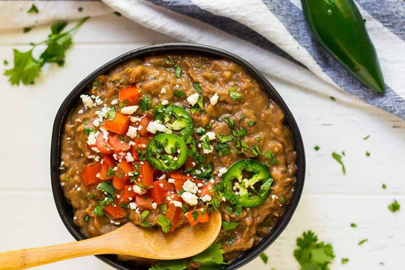 Instant pot refried beans topped with sliced jalapenos in black bowl on counter