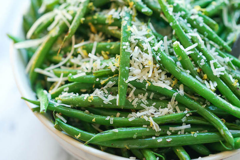 Green beans topped with grated parmesan cheese on plate on counter