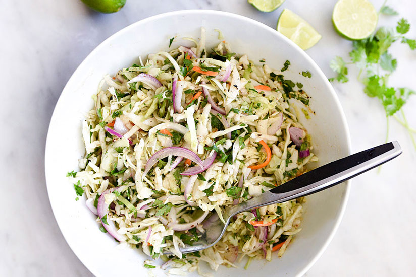 Mexican coleslaw with sliced red onions in white bowl on marble counter