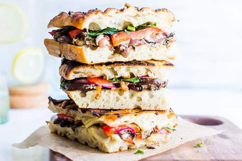 Three mushroom and goat cheese panini sandwiches stacked on wood tray