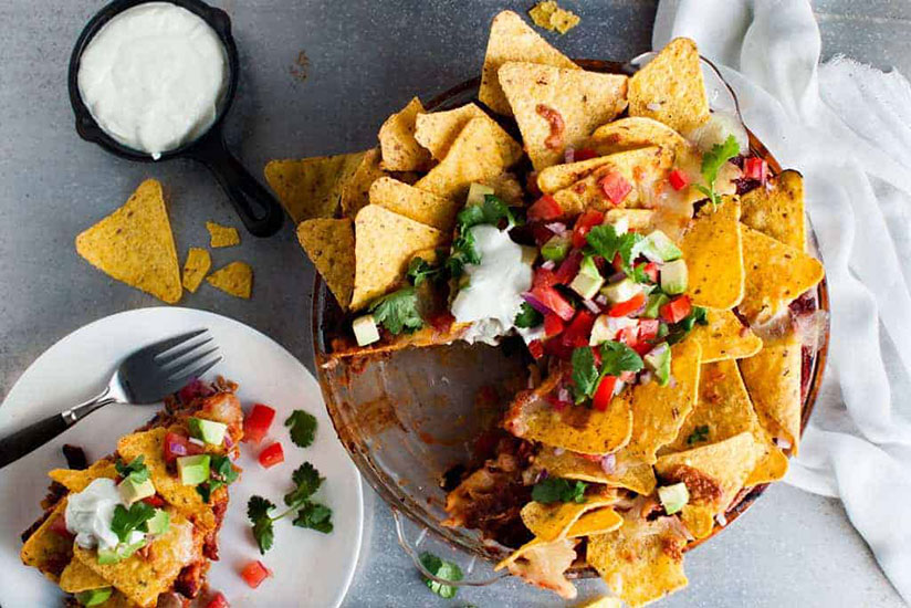 Consumed nacho pie topped with tortilla chips and salsa in clear dish on counter