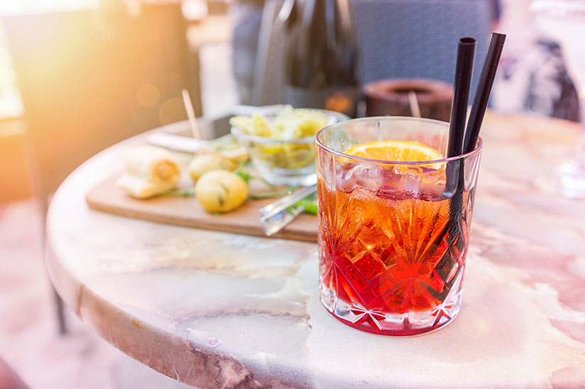 Negroni cocktail with black straws on table in open restaurant on background