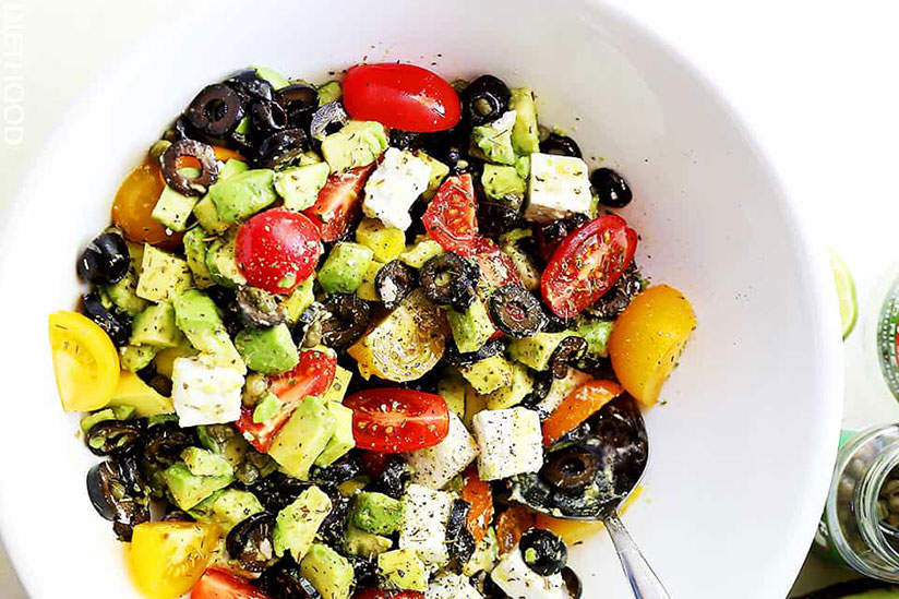 Olives, avocado, and tomato salad with feta cheese in white bowl on countrer