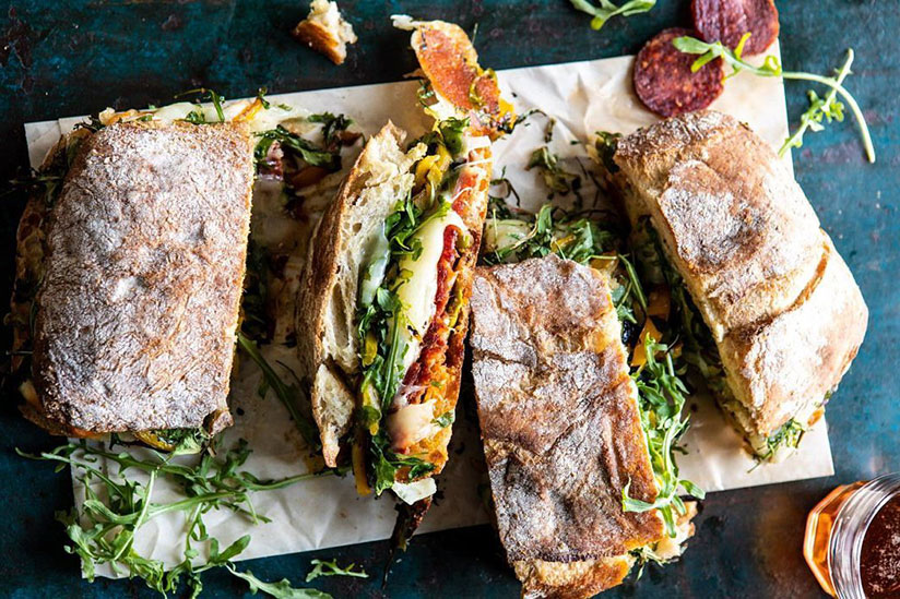 Sliced Italian melt with prosciutto and arugula on top of sandwich paper