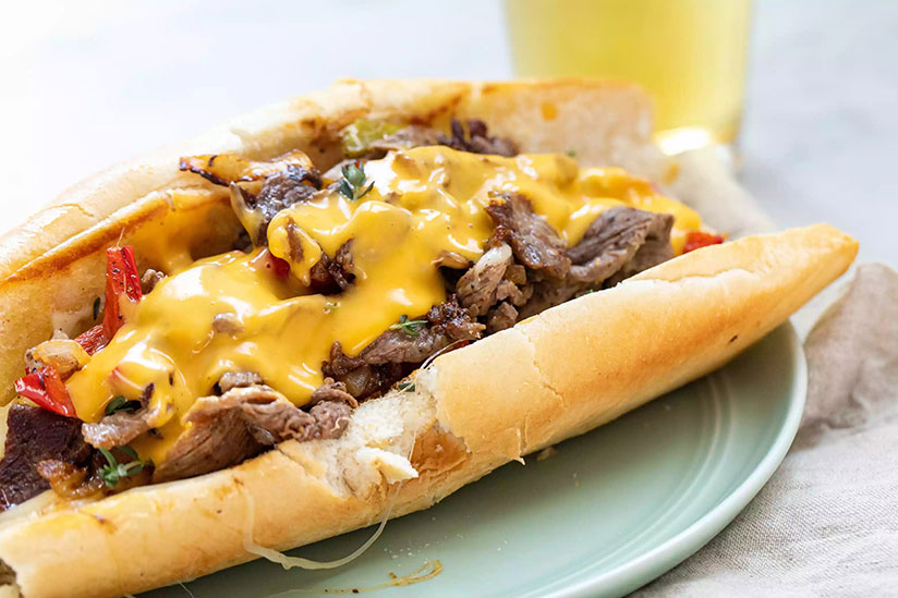 Philly cheesesteak in hotdog bun topped with cheese wiz on green plate