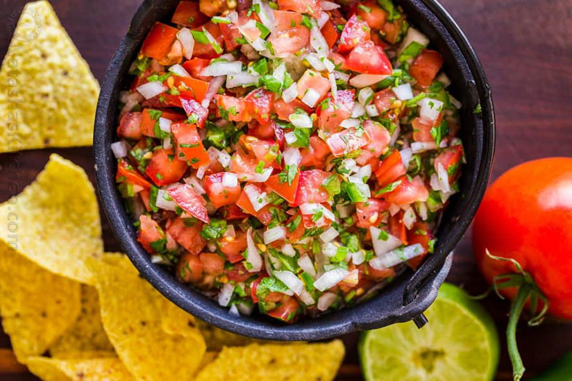 Pico de gallo in black bowl surrounded by tortilla chips on wood tray