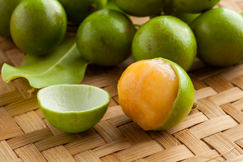 Bunch of quenepa fruits on top of woven tray with one already peeled and ready to eat