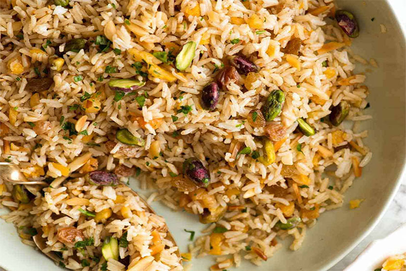 Rice pilaf with dried fruits, almonds, and pistachios on plate on counter