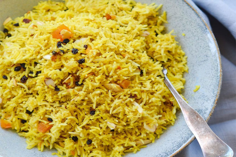 Basmati rice with dried fruits and sliced almonds on blue plate with spoon