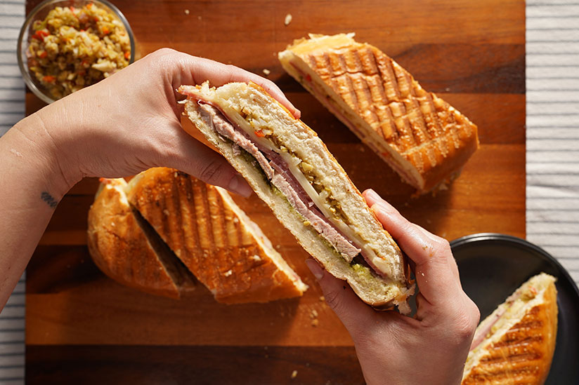 Roast pork panini held with two hands with remaining slices on background