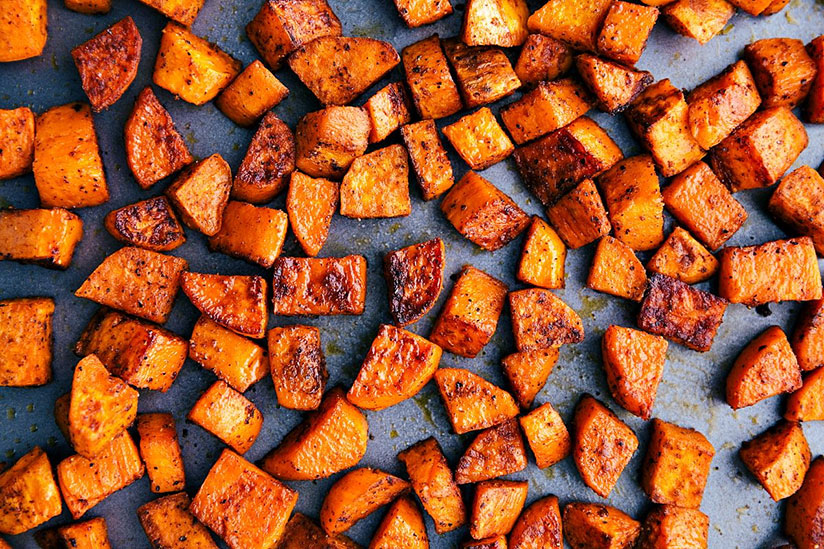 Oven roasted cubed sweet potatoes on metal tray on counter