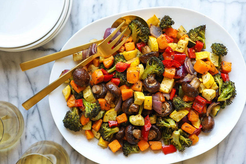 Roasted vegetables in white dish with gold spoon and fork on marble counter