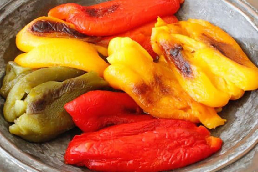 Green, yellow, and red roasted bell peppers in gray bowl