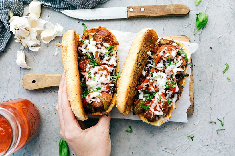 Hand cupping Italian sausage hoagies topped with homemade sauce on wood tray