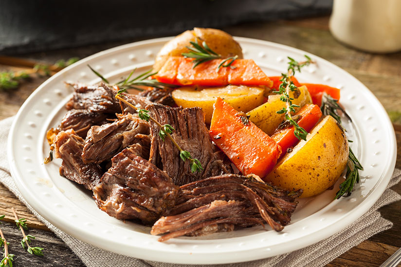 Slow cooked pot roast with carrots and potatoes on white plate on wood table
