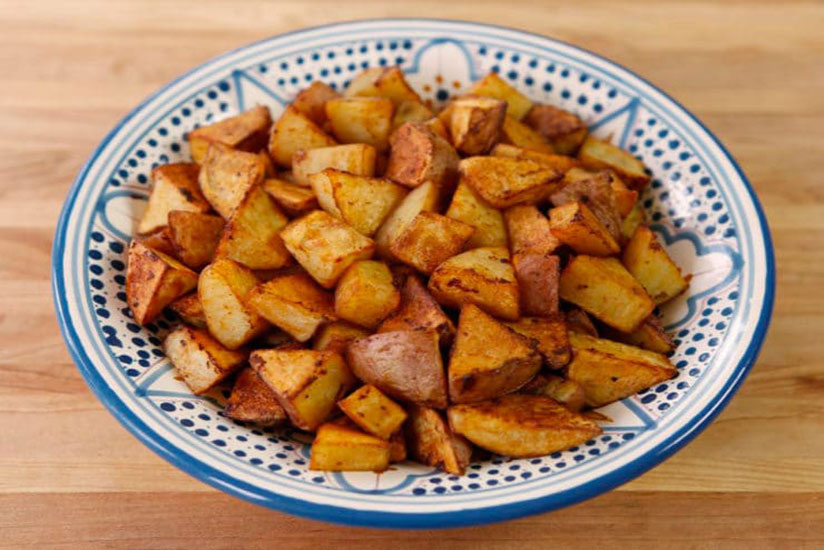 Cubed smoked paprika roasted potatoes in blue and white bowl on wood counter