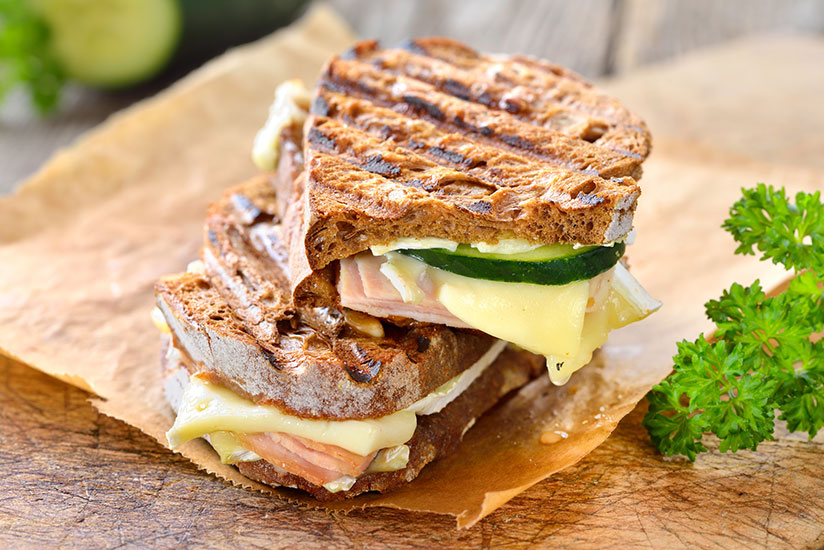 Smoked turkey and melted brie cheese panini on sandwich paper on counter