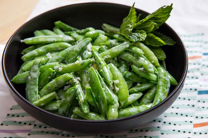 Snap pea salad in black bowl on tablecloth on white wood table