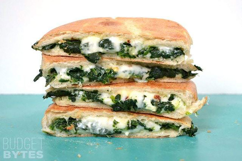 Stack of spinach grilled cheese paninis on green counter on white background